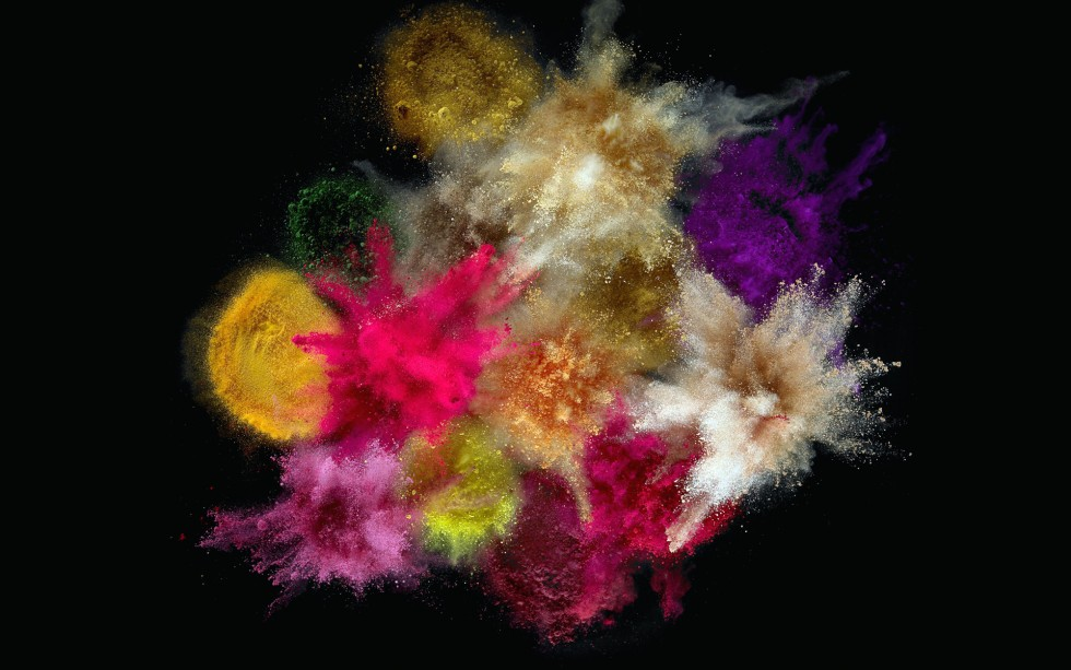 Close-up of colorful powder splashing against black background